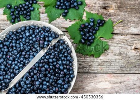 Fresh fruits of blueberry in basket, ripe berries from forest on wooden background, top view - stock photo