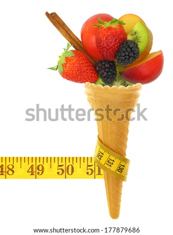 Fresh fruits on ice cream cone with tape measure - stock photo