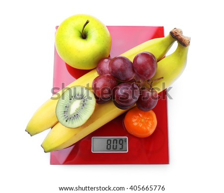 Fresh fruits on red digital kitchen scales, isolated on white