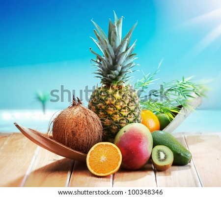 Fresh Fruits on the beach at a deck in front of an island with a palm. Assorted tropical fruits, orange,Ananas or pineapple, lime,mango and avocado. - stock photo
