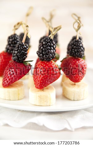 Fresh fruits on the skewers. Shallow depth of field - stock photo