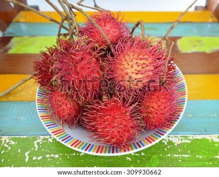 Fresh Fruits, Ripe and Sweet Refreshing rambutan on colourful wood chair, Thailand fruit name Rambutan - stock photo