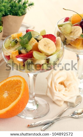 Fresh fruits salad and strawberries on wooden table - stock photo