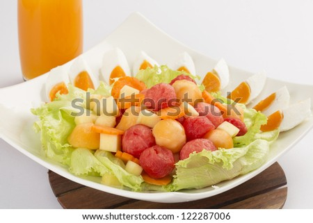 Fresh fruits salad on white dish - stock photo