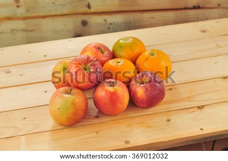 Fresh fruits such as oranges, red apples on the table with wooden background - stock photo