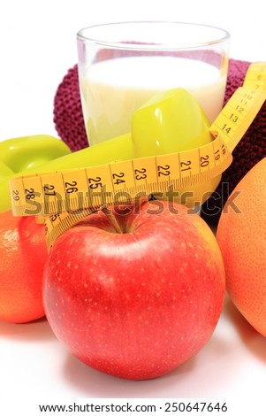 Fresh fruits, tape measure, glass of milk, green dumbbells and purple towel for using in fitness, concept for slimming, healthy nutrition and lifestyle