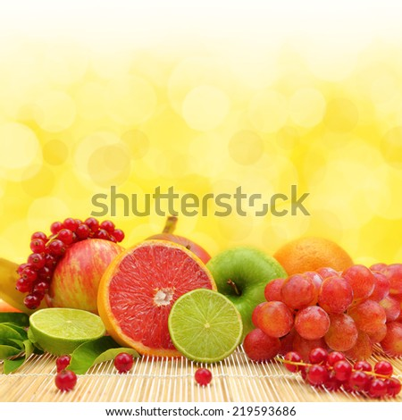 Fresh fruits with yellow background and bokeh, copy-space - stock photo