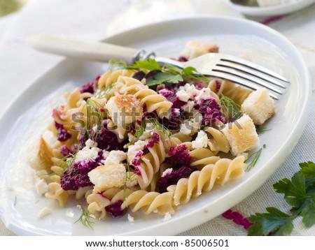Fresh fusilli pasta with beet pesto and cheese. Selective focus - stock photo