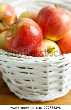 Fresh Gala Apples in a white wicker basket.