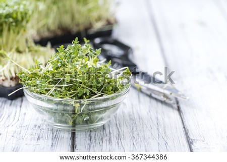 Fresh Garden Cress as close-up shot with selective focus on wooden background - stock photo