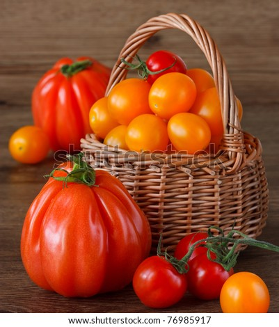 Fresh garden tomatoes in a wicker basket. - stock photo