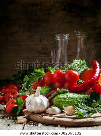 Fresh garlic, cherry tomatoes, cucumber, hot pepper, parsley, dill on a wooden cutting board, vegetables for the Mediterranean diet, selective focus