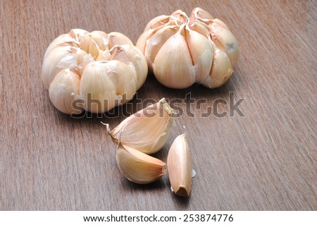 Fresh garlic isolated on brown table - stock photo