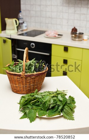 Fresh gathered nettles in a wicker basket on the table in the kitchen - stock photo