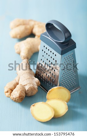 fresh ginger and grater over blue - stock photo