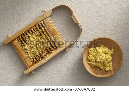 Fresh ginger granules in washboard and wooden plate