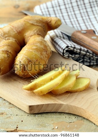 Fresh ginger root on a cutting board - stock photo