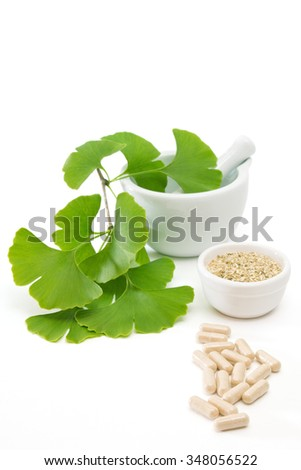 Fresh ginkgo leaves in a mortar with dried herb and capsules on white background