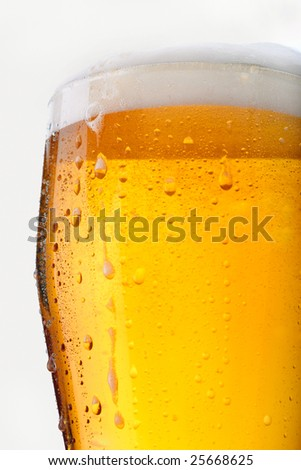 Fresh glass of beer with froth and condensed water pearls on white background