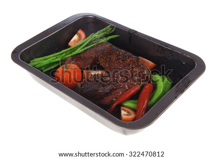 fresh glazed baked big beef meat rib chunk under sweet sauce with tomatoes hot chili pepper pink peppercorn and asparagus in black tray isolated on white background - stock photo