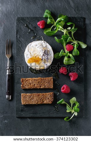 Fresh goat cheese served on black slate board with honey, honeycomb, lavender, raspberries and green salad. With vintage fork. Flat lay. - stock photo