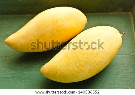 Fresh golden mango on wood table - stock photo