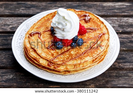 Fresh golden pancakes with cream and chocolate, fruit - stock photo