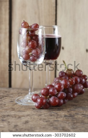 fresh grape in wine glass and glass of red wine on wooden background.