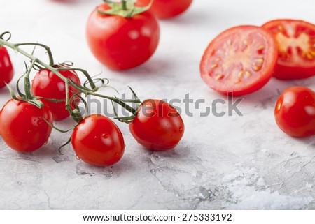 Fresh grape tomatoes with sea salt  with a halved tomato in the foreground. Stone background - stock photo