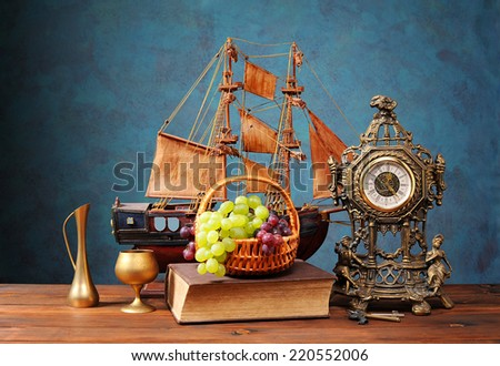 Fresh grapes in a wicker basket and a clock on the table - stock photo