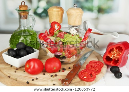 Fresh greek salad in glass bowl surrounded by ingredients for cooking on wooden table on window background close-up - stock photo