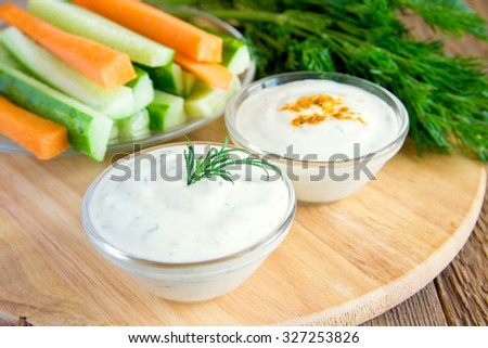 fresh Greek Tzatziki yogurt dip (sauce) and assorted vegetables on wooden table