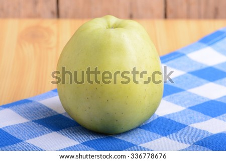 Fresh green apple on blue material background - stock photo