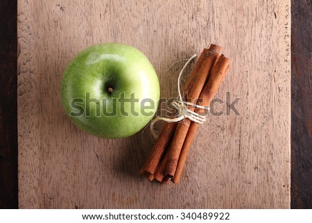 fresh green apples and bunch of cinnamon on wooden background