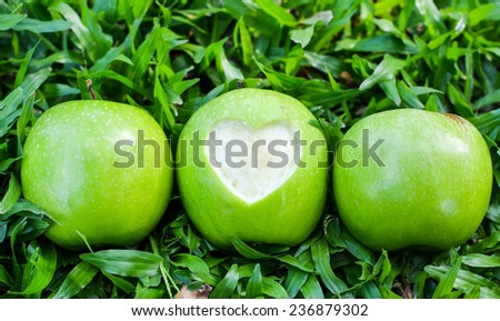 Fresh green apples with cut off heart shape on green grass background - stock photo