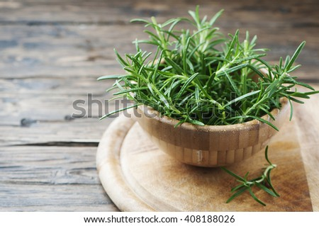 Fresh green aromatic rosemary on the wooden table, selective focus