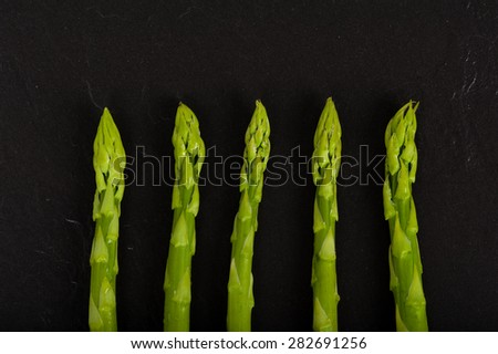 Fresh green Asparagus on Slate. Close up.  - stock photo