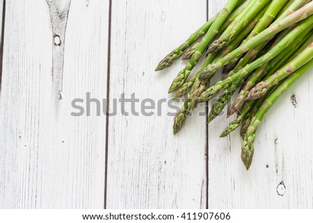 Fresh green asparagus on white  wooden background, top view. Space on left side. - stock photo