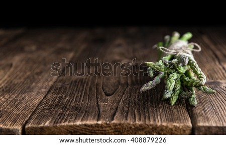 Fresh green Asparagus (selective focus, close-up shot) on wooden background - stock photo