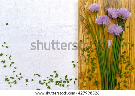 Fresh green blooming chives with purple flowers, chopped on white background - stock photo