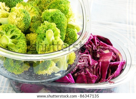 fresh green broccoli and magenta cabbage in steamer utensils