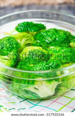 Fresh green broccoli in bowl with water on rustic wooden background. Healthy or vegetarian food concept