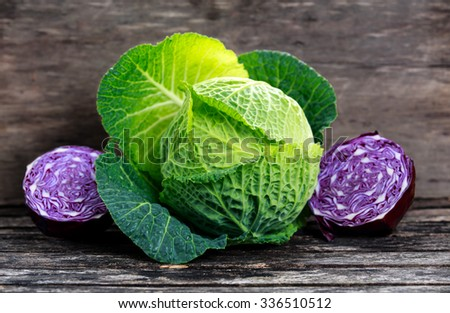Fresh Green cabbage and slice of Red cabbage on old wooden table - stock photo