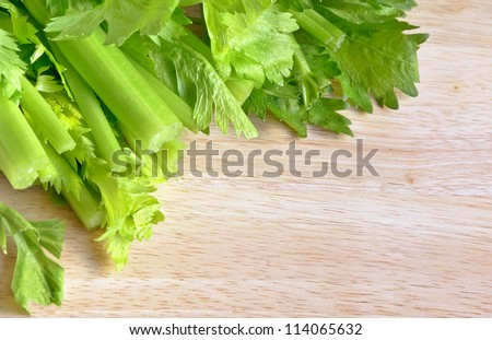 Fresh green celery on a wooden cutting board. - stock photo