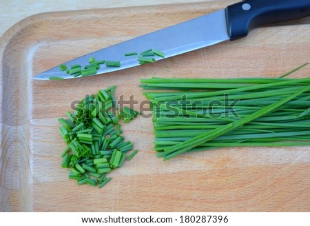 Fresh green chopped chives on wooden plate - stock photo