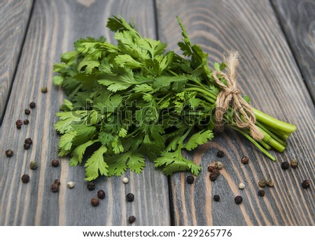 Fresh green coriander on a wooden background - stock photo