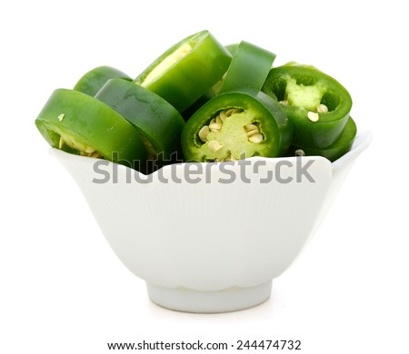 fresh green cut chili pepper pieces on white bowl - stock photo