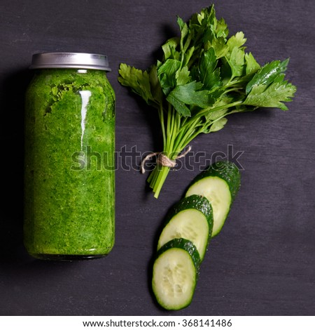 fresh green detox smoothie in bottle with parsley and cucumber