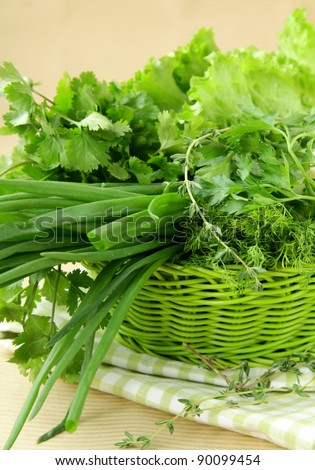 fresh green grass parsley dill onion herbs mix in a wicker basket - stock photo