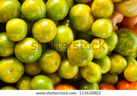 Fresh green heirloom tomatoes on display at the market - stock photo